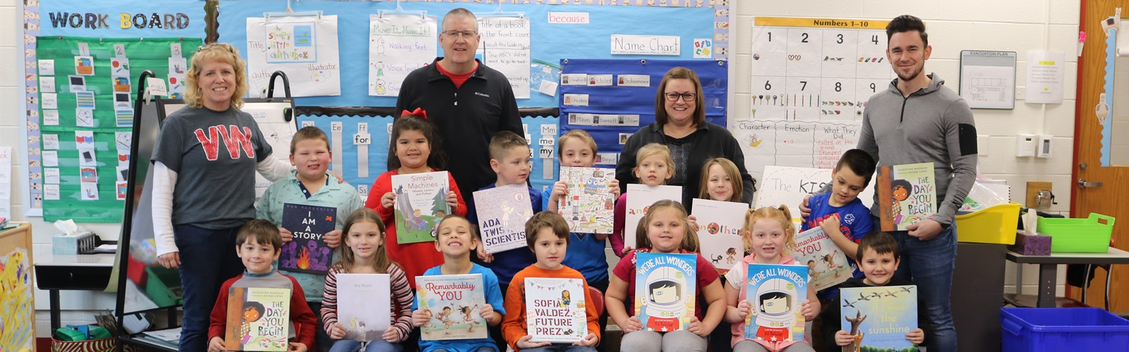 Mrs. Foster's class posing with books that were received as part of a grant