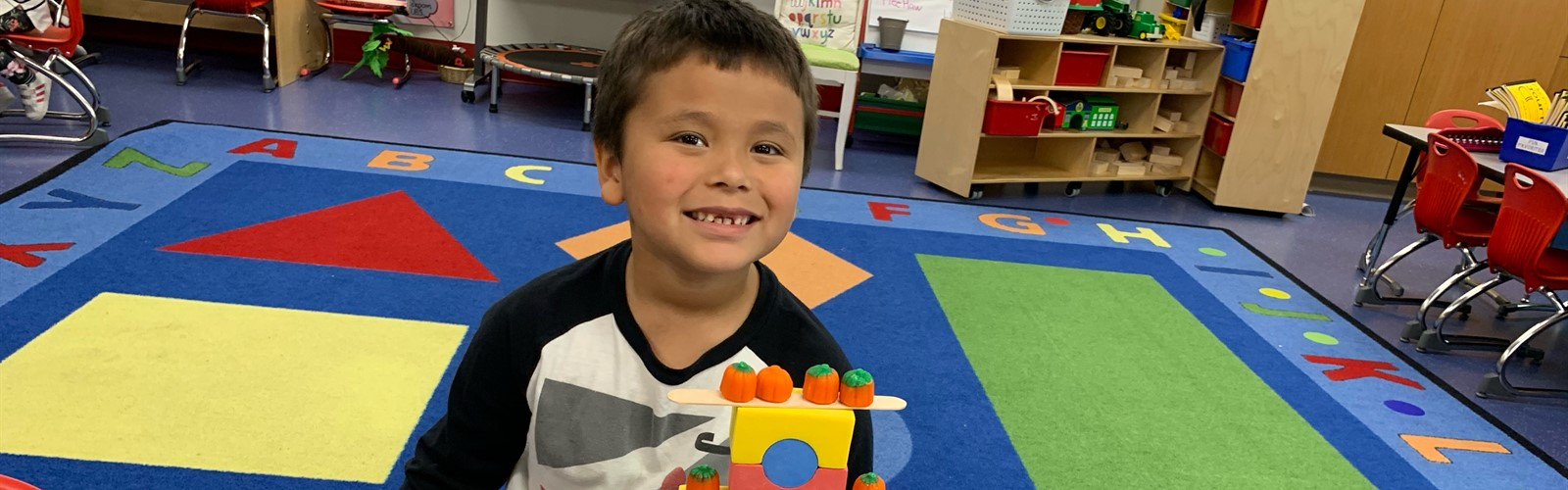 Preschool student sits at table with structure he built with blocks and small pumpkins.