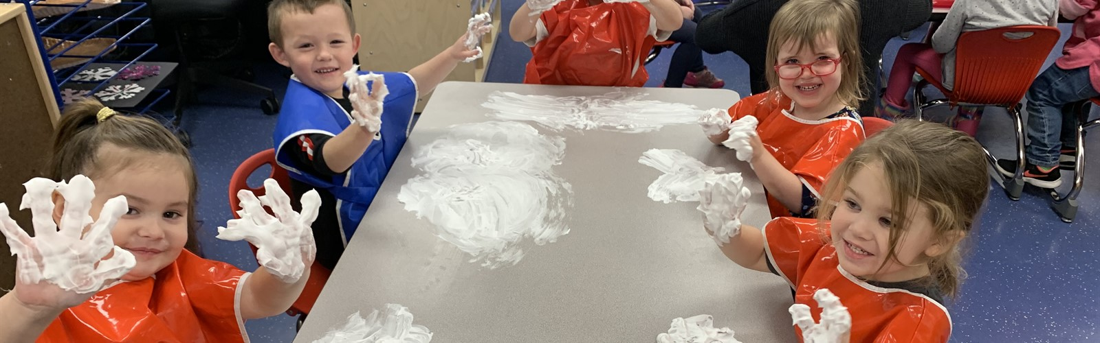 Preschool students hold up their hands with shaving cream on them. They are enjoying a sensory experience and practicing writing letters and drawing shapes.