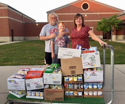 Tristan and his family pose with the 400 items they donated to the middle school food drive